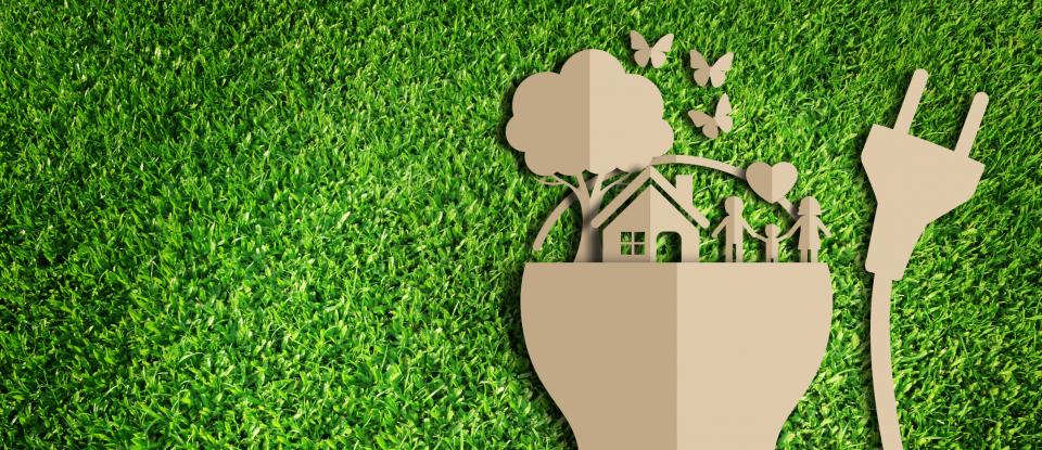Paper cutout of Light Bulb with Home on Green Grass (Symbolizes Green Energy)