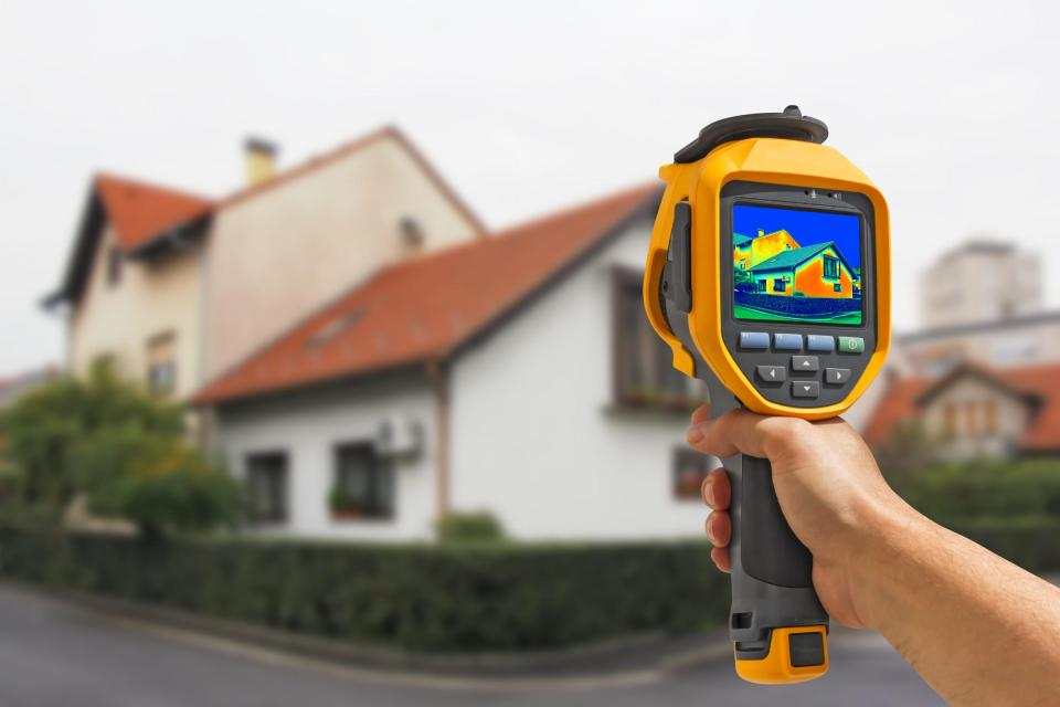 Hand Holding Thermal Imager in Front of House